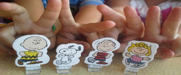 The kids photobombing the game pieces from Wonder Forge's Peanuts Surprise Slides