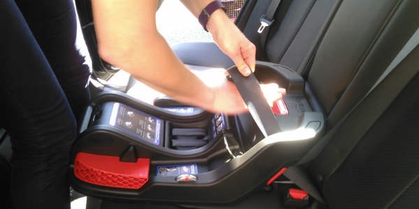 Danielle Bojanzyk , the safety engineer and SnugKid technician for Nissan. shows how to fasten a safety seat.